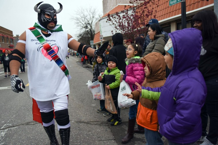 Parade-goers high five a man dressed as a Lucha libre wrestler during the 52nd annual Cinco de Mayo parade Sunday, May, 1, 2016, in Detroit's Southwest community. Cinco de Mayo commemorates the May 5, 1862 defeat of the invading French army by Mexican forces at Puebla. (Tanya Moutzalias/The Ann Arbor News via AP)