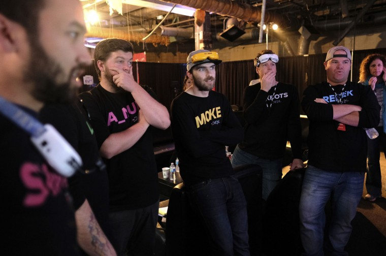 In this Saturday, March 19, 2016, photo, pilots from the Drone Racing League watch a race on a large TV backstage at a vacant mall in Hawthorne, Calif. Drone racing leagues would love to follow sports like poker into the mainstream with big TV audiences and sponsorships. But getting sponsors and fans is also a race against time. (AP Photo/Richard Vogel)