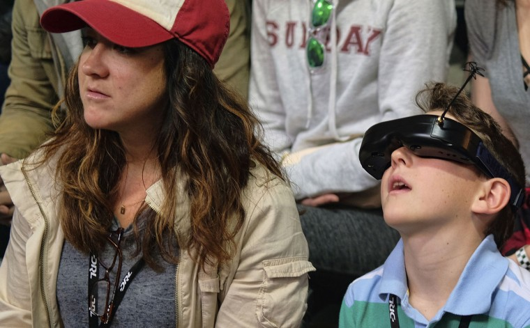 In this Saturday, March 19, 2016, photo, Valentina Valentini and her nephew James Lemon, who's wearing First Person View goggles, watch a drone racing during a race of the Drone Racing League in a vacant mall in Hawthorne, Calif. (AP Photo/Richard Vogel)