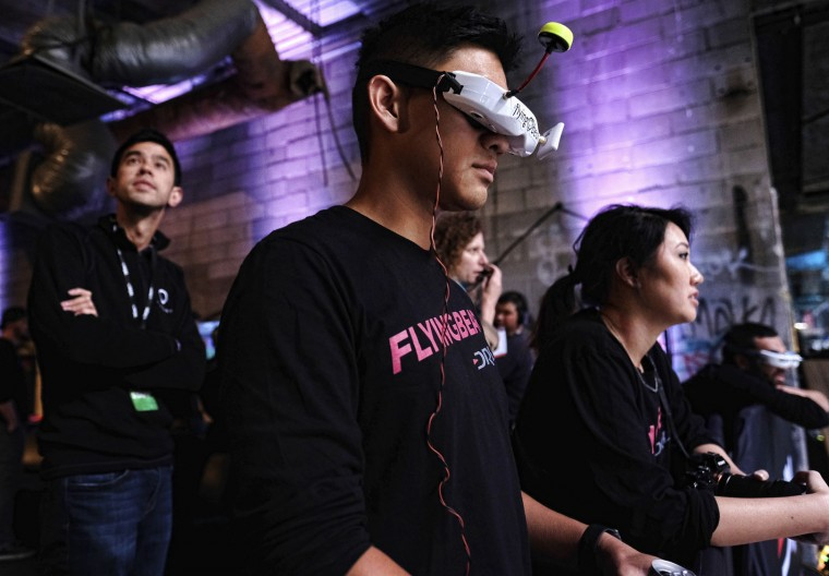 "In this March 19, 2016, photo, Fred ""Flying Bear"" Loo watches a drone race with other pilots during a Drone Racing League event in Hawthorne, Calif. Loo, an engineer for a Silicon Valley technology giant, says he's burned through vacation days, lunch hours and weekends flying drones. (AP Photo/Richard Vogel)"