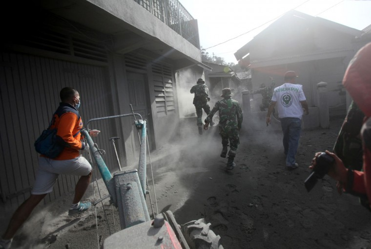 Rescuers rush to help villagers to evacuate their homes following the eruption of Mt. Sinabung in Gamber village, North Sumatra, Indonesia, Sunday, May 22, 2016. The volcano in western Indonesian unleashed hot clouds of ash on Saturday, killing several villagers, an official said. (AP Photo/Binsar Bakkara)