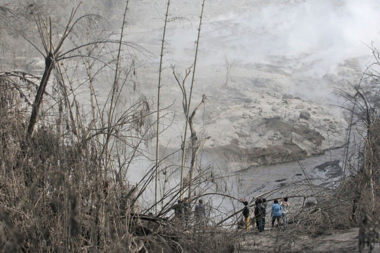 Villagers inspect the path of a pyroclastic flow from the eruption of Mount Sinabung in Gamber village, North Sumatra, Indonesia, Sunday, May 22, 2016. The volcano in western Indonesian unleashed hot clouds of ash on Saturday, killing several villagers, officals said. (AP Photo/Binsar Bakkara)