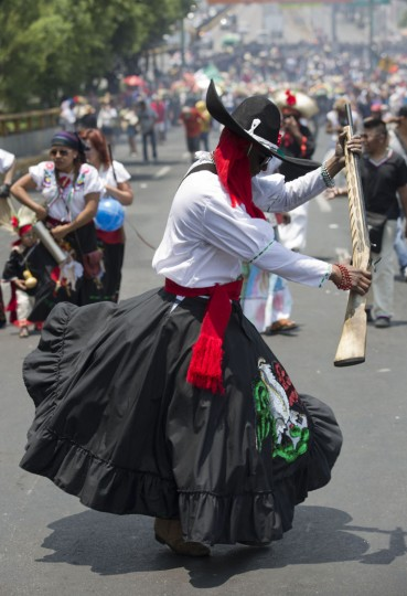A man dressed as a revolutionary Zacapoaztla Indian soldier dances during a re-enactment of the battle of Puebla between the Zacapoaztlas Indians and French army at the Cinco de Mayo celebrations, in the Penon de los Banos neighborhood of Mexico City, Wednesday, May 5, 2016. Cinco de Mayo commemorates the victory of an ill-equipped Mexican army over French troops in Puebla on May 5, 1862. (AP Photo/Eduardo Verdugo)