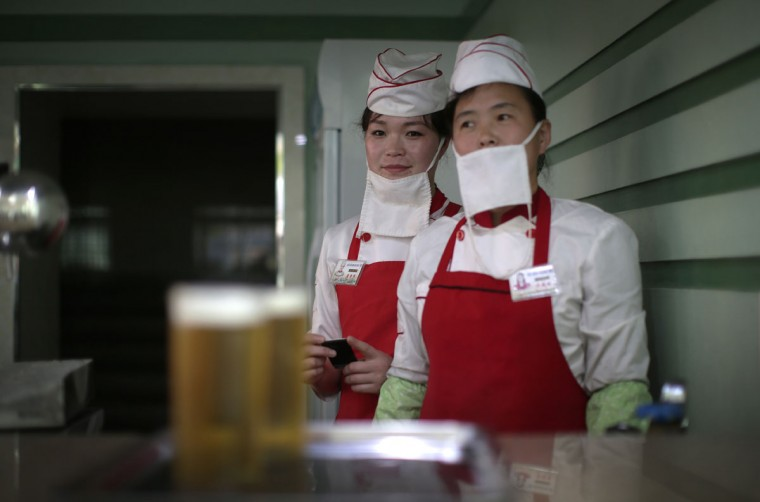 "In this Saturday, May 7, 2016, photo, beer servers Kim Yon Hui, 29, left, and Yang Pok Yong, 42, right wait to serve customers at the Taedonggang Beer shop in Pyongyang, North Korea. Ahead of the ongoing congress of North Korea's ruling Workers' Party, the nation was called upon to do massive overtime to boost production and show their devotion to leader Kim Jong Un in a 70-day ""loyalty campaign."" And that's in addition to the hour after hour of rehearsals for huge rallies when their ruling party wraps up its first congress in decades. So how does a tired North Korean unwind? Beer. Beer. And more beer. (AP Photo/Wong Maye-E)"