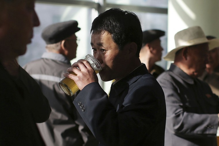 "In this Saturday, May 7, 2016, photo, North Korean men drink beer at the Taedonggang Beer shop in Pyongyang, North Korea. Ahead of the ongoing congress of North Korea's ruling Workers' Party, the nation was called upon to do massive overtime to boost production and show their devotion to leader Kim Jong Un in a 70-day ""loyalty campaign."" And that's in addition to the hour after hour of rehearsals for huge rallies when their ruling party wraps up its first congress in decades. So how does a tired North Korean unwind? Beer. Beer. And more beer. (AP Photo/Wong Maye-E)"