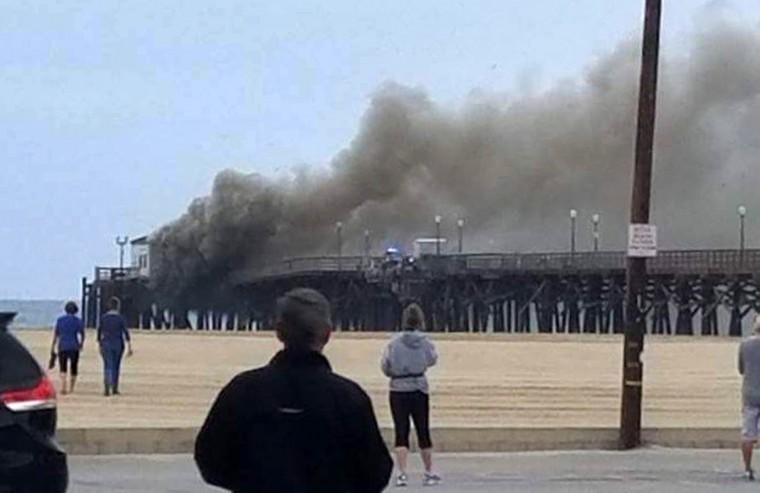 This photo provided by Amy Stanton shows a large plum of smoke from a fire burning on the Seal Beach pier in Seal Beach, Calif., on Friday, May 20, 2016. A fire is burning on a former restaurant on Southern California's Seal Beach Pier. The blaze erupted early Friday at the end of the long wooden pier southeast of Los Angeles. Harbor patrol boats are attacking the flames with streams from water cannons while firefighters direct streams from hoses on the pier. (Amy Stanton via AP)