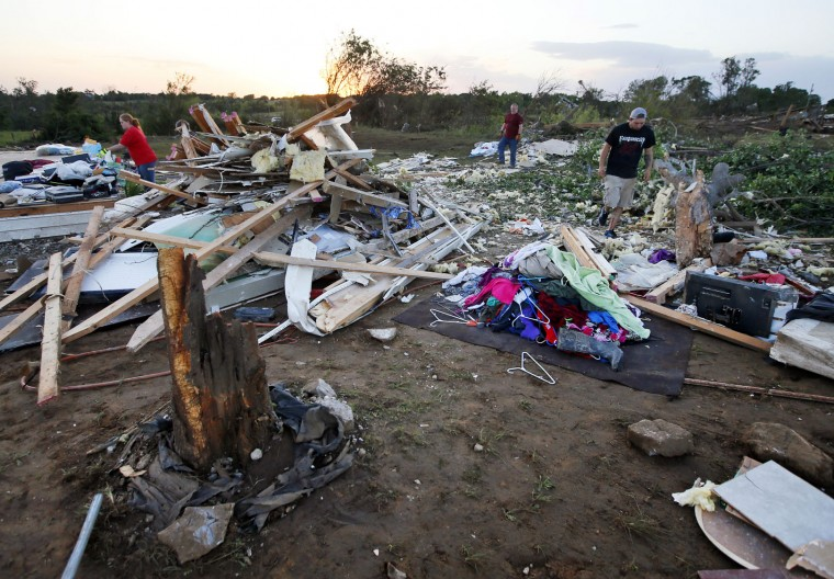 Friends and family of Lisa Buckner, not pictured, help to clean up after a tornado destroyed Buckner's home west of Wynnewood, Okla., in rural Gavin County, Monday, May 9, 2016. Storms swept through the nation's midsection Monday, spawning numerous tornadoes. (Nate Billings/The Oklahoman via AP)