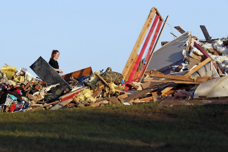 A woman looks over tornado damage west of Wynnewood, Okla., in rural Gavin County, Monday, May 9, 2016. Storms swept through the nation's midsection Monday, spawning numerous tornadoes. (Nate Billings/The Oklahoman via AP)