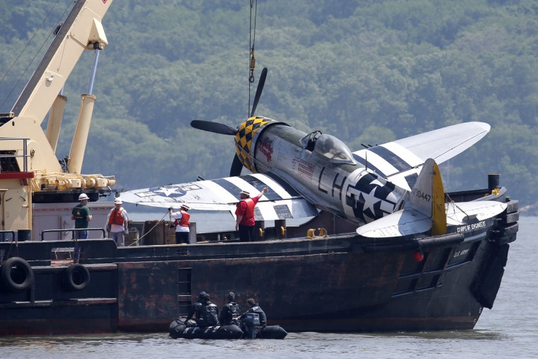 Officials remove a plane out of the Hudson River a day after it crashed, Saturday, May 28, 2016, in North Bergen, N.J. The World War II vintage P-47 Thunderbolt aircraft crashed into the river Friday, May 27, 2016, killing its pilot. (AP Photo/Julio Cortez)