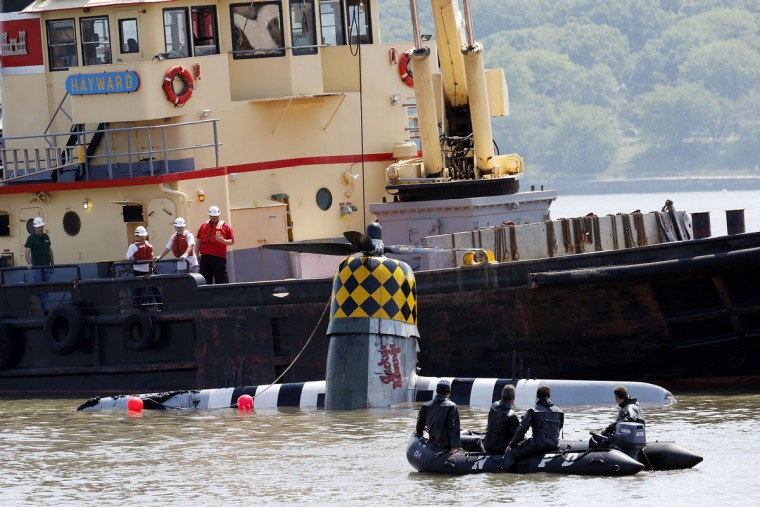 Officials remove a plane out of the Hudson River a day after it crashed, Saturday, May 28, 2016, in North Bergen, N.J. The World War II vintage P-47 Thunderbolt aircraft crashed into the river Friday, May 27