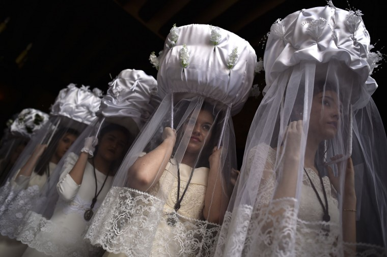 Participants of ''Bread Procession of the Saint'', take part in the ceremony in honor of Domingo de La Calzada Saint (1019-1109) in Santo Domingo de La Calzada, northern Spain, Wednesday, May 11, 2016. Every year during spring season, ''Las Doncellas'' (White Virgins), hold on their head a basket covered with white cloth while they walk through this old village in honor of the saint. (AP Photo/Alvaro Barrientos)