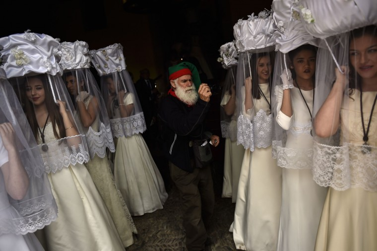 A pilgrim takes photos of participants of the ''Bread Procession of the Saint'', in the ceremony in honor of Domingo de La Calzada Saint (1019-1109) in Santo Domingo de La Calzada, northern Spain, Wednesday, May 11, 2016. Every year during spring season, ''Las Doncellas'' (White Virgins), hold on their head a basket covered with white cloth while they walk through this old village in honor of the saint. (AP Photo/Alvaro Barrientos)