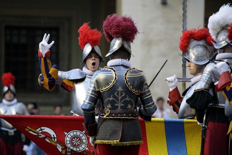 Vatican Swiss guards, one of them holding up his right arm and showing three fingers to represent the Holy Trinity, attend a swearing-in ceremony, at the Vatican, Friday, May 6, 2016. The ceremony is held each May 6 to commemorate the day in 1527 when 147 Swiss Guards died protecting Pope Clement VII during the Sack of Rome. (AP Photo/Andrew Medichini)