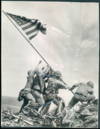 "The iconic AP shot by Joe Rosenthal. A caption reads, ""IWO JIMA.... THE SPIRIT OF '45: In a scene more like the work of a sculptor than an actual news photograph, Marines of the 28th regiment, fifth division, hoist the American flag..."""