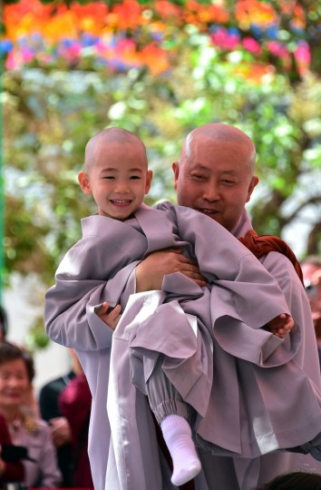 A South Korean child is lifted by a Buddhist monk after having his head shaved during a ceremony entitled 'Children Becoming Buddhist Monks', at the Jogye temple in Seoul on May 2, 2016. (JUNG YEON-JE/AFP/Getty Images)