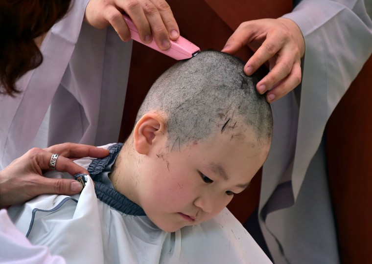 A South Korean child has his head shaved by Buddhist monks during a ceremony entitled 'Children Becoming Buddhist Monks', at the Jogye temple in Seoul on May 2, 2016. (JUNG YEON-JE/AFP/Getty Images)