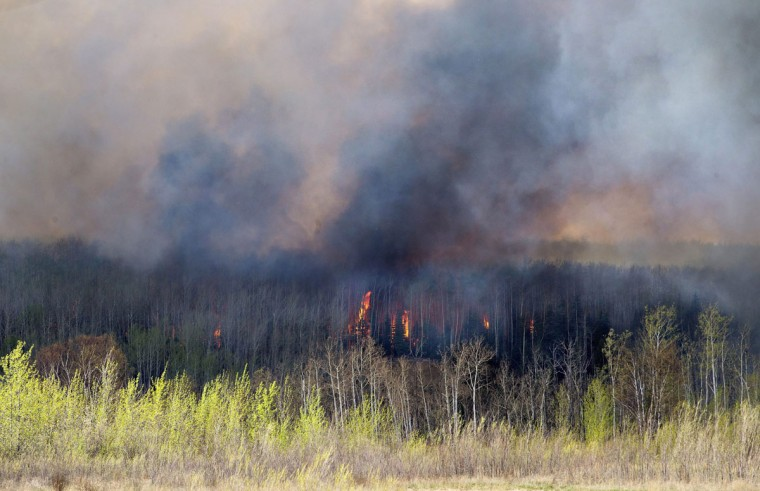 A wildfire rages through Fort McMurray, Alberta, Wednesday, May 4, 2016. The raging wildfire emptied Canada's main oil sands city, destroying entire neighborhoods of Fort McMurray, where officials warned Wednesday that all efforts to suppress the fire have failed. (Jason Franson /The Canadian Press via AP)