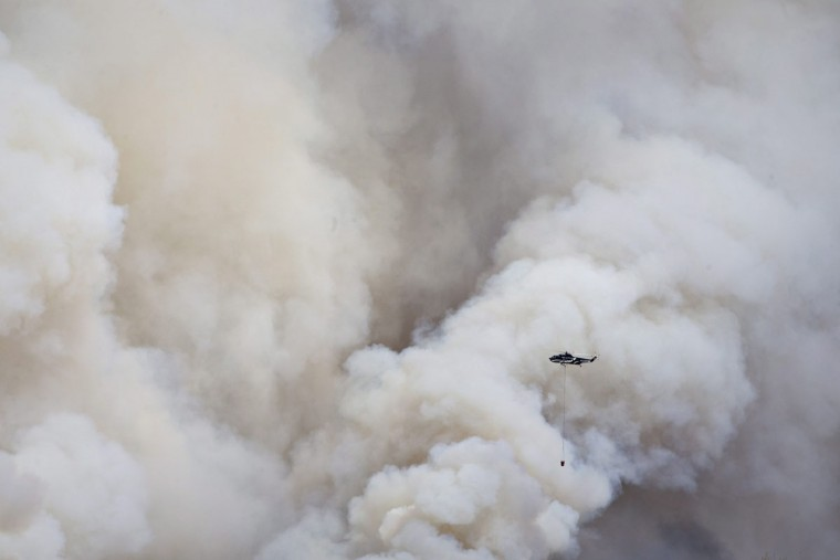 A helicopter battles a wildfire in Fort McMurray Alberta, on Wednesday, May 4, 2016. The raging wildfire emptied Canada's main oil sands city, destroying entire neighborhoods of Fort McMurray, where officials warned Wednesday that all efforts to suppress the fire have failed. (Jason Franson /The Canadian Press via AP)