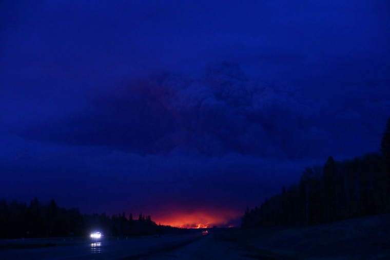 A plume of smoke hangs in the air as forest fires rage on in the distance in Fort McMurray, Alberta on May 4, 2016. Numerous vehicles can be seen abandoned on the highways leading from the raging forest fires in Fort McMurray and neighbouring communities have banded together to offer support in the form of food, water, and gasoline. (COLE BURSTON//AFP/Getty Images)