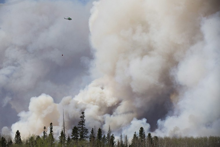 A helicopter battles a wildfire in Fort McMurray Alberta on Wednesday May 4, 2016. The raging wildfire emptied Canada's main oil sands city, destroying entire neighborhoods of Fort McMurray, where officials warned Wednesday that all efforts to suppress the fire have failed. (Jason Franson /The Canadian Press via AP)