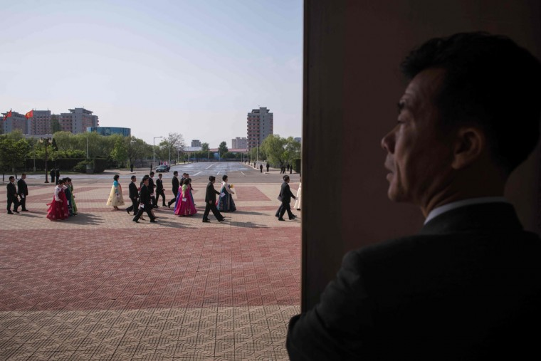 A government guide watches as attendees of the 7th Workers Party Congress arrive for a cultural performance in Pyongyang on May 11, 2016. North Korea's rare ruling party congress was seen as a chance for young leader Kim Jong-Un to bolster his power, some four years after succeeding his late father. (ED JONES/AFP/Getty Images)