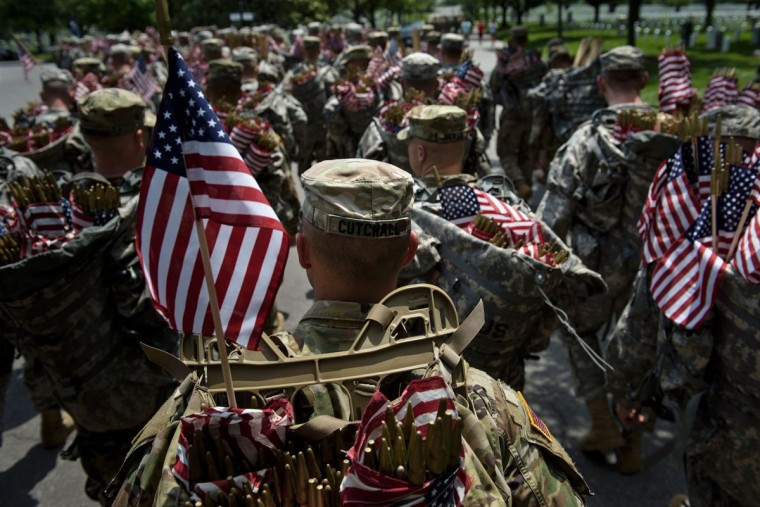 Members of the US Army march with miniature American flags to place at graves in Arlington National Cemetery on May 26, 2016 in preparation for Memorial Day in Arlington, Virginia. (BRENDAN SMIALOWSKI/AFP/Getty Images)