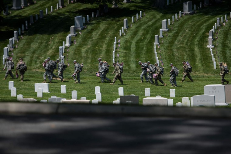 Members of the US Army walk to place American flags at graves in Arlington National Cemetery on May 26, 2016 in Arlington, Virginia in preparation for Memorial Day. (BRENDAN SMIALOWSKI/AFP/Getty Images)