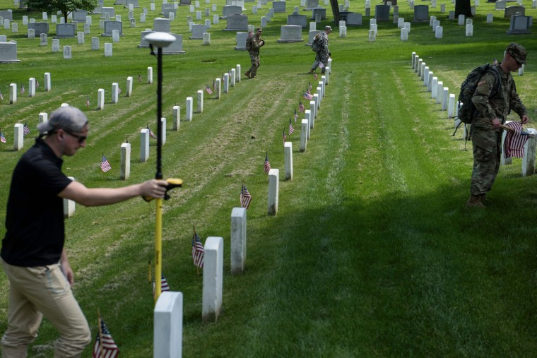 A man uses GPS to plot a grave's location on May 26, 2016, while members of the US Army place American flags at graves at Arlington National Cemetery, Arlington, Virginia in preparation for Memorial Day. (BRENDAN SMIALOWSKI/AFP/Getty Images)
