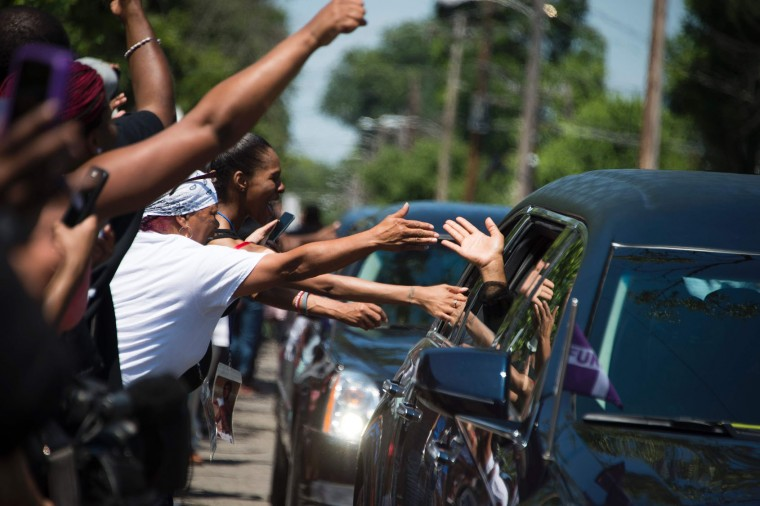 People reach out to the limousines in boxing legend Muhammad Ali's procession as it drives past his childhood home where mourners waited to pay their respects on June 10, 2016 in Louisville, Kentucky. Thousands of people from near and far were expected to line the streets of Muhammad Ali's hometown Louisville on Friday to say goodbye to the boxing legend and civil rights hero, who mesmerized the world with his dazzling skills. (Jim Watson/AFP/Getty Images)