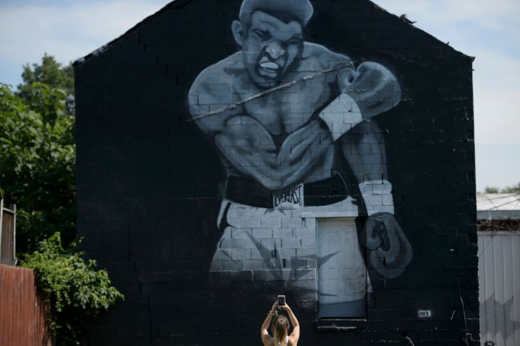 A woman photographs a mural of Muhammad Ali's 1965 victory over Sonny Liston June 10, 2016 in Louisville, Kentucky. A mass funeral procession for Muhammad Ali began Friday in his hometown Louisville, with a hearse carrying the boxing legend's remains heading into the streets where thousands gathered to say goodbye. (Brendan Smialowski/AFP/Getty Images)
