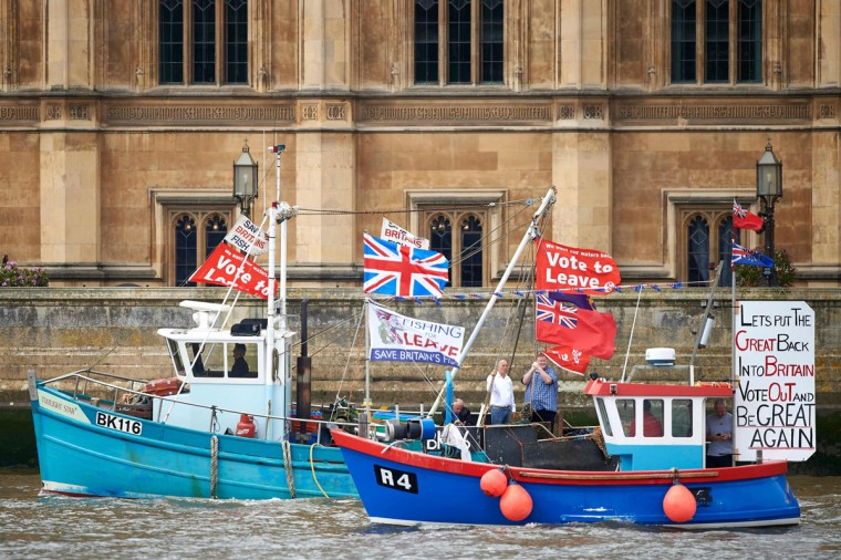 "Boats decorated with flags and banners from the 'Fishing for Leave' group that are campaigning for a 'leave' vote in the EU referendum sail by the British Houses of Parliament as part of a ""Brexit flotilla' on the river Thames in London on June 15, 2016. A Brexit flotilla of fishing boats sailed up the River Thames into London today with foghorns sounding, in a protest against EU fishing quotas by the campaign for Britain to leave the European Union. (AFP PHOTO / NIKLAS HALLE'N)"