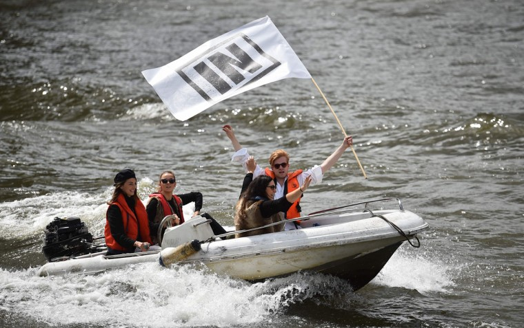 A boat carrying supporters for the Remain in the EU campaign shout and wave at Brexit fishing boats as they sail up the river Thames in central London on June 15, 2016. A Brexit flotilla of fishing boats sailed up the River Thames into London today with foghorns sounding, in a protest against EU fishing quotas by the campaign for Britain to leave the European Union. (AFP PHOTO / BEN STANSALL)