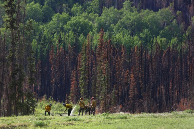 Forest rangers work on hot spots along Highway 63 outside of Fort McMurray, Alberta on June 1, 2016. Tens of thousands of Fort McMurray residents were expected to begin trickling back into the Canadian oil city ravaged by wildfires Wednesday after the blaze was declared no longer a threat. (Cole Burston/AFP/Getty Images)