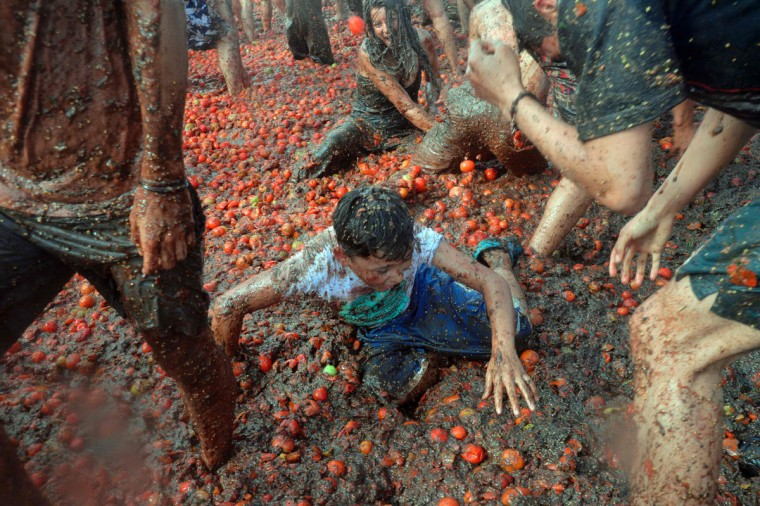 "People participate in the 10th annual tomato fight festival, known as ""tomatina"", in Sutamarchan, Boyaca department, Colombia, on June 5, 2016. (GUILLERMO LEGARIA/AFP/Getty Images)"