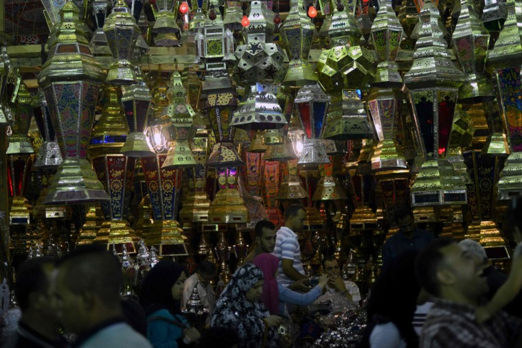 "Egyptians walk past traditional lanterns known in Arabic as ""Fanous"", sold during the Muslim holy month of Ramadan, in the Saida Zeinab district in the capital Cairo, as the faithful prepare for the start of the holy month, on May 29, 2016. More than 1.5 billion Muslims around the world will mark the holy month which begins this week. Ramadan is the ninth month of the Muslim lunar calendar during which observant Muslims fast from dusk to dawn. / (AFP Photo/Mohamed El-shahed)"