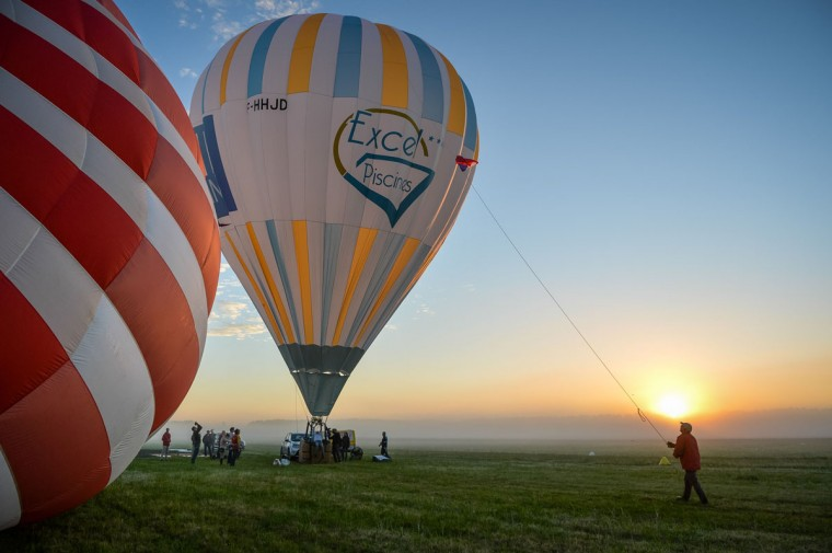 Preparations are made before French trapeze artist Isabelle Ponsot takes off in a hot air balloon to perform while hanging from the balloon above Chatellerault on June 22, 2016. (GUILLAUME SOUVANT/AFP/Getty Images)