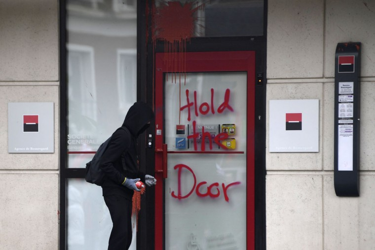 A protester tags a bank door as he protests against the government's labour market reforms in Rennes, northwestern France, on June 2, 2016. Thousands took to the streets across the country on Thursday in the latest demonstrations against the labour law reforms, which the government says are designed to make France more business-friendly. In Rennes, the police charged the protesters with the help of vehicles, leaving several injured. (Damien Meyer/AFP/Getty Images)