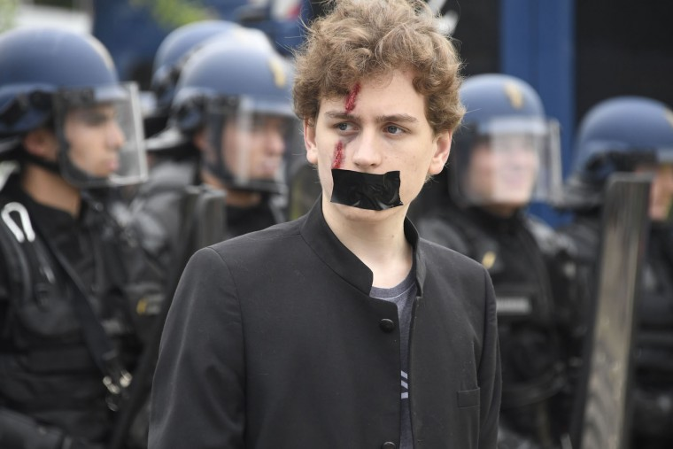 A gagged man with a makeup scar looks on as he protests against the government's labour market reforms in Rennes, northwestern France, on June 2, 2016. Thousands took to the streets across the country on Thursday in the latest demonstrations against the labour law reforms, which the government says are designed to make France more business-friendly. (Damien Meyer/AFP/Getty Images)