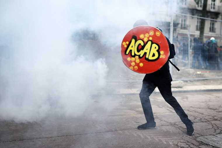 "A man holds a shield reading ""ACAB : All cops are bastards"" during clashes with French riot police during a demonstration against the government's planned labour law reforms on June 2, 2016 in Nantes, western France. More demonstrations against the reforms which the government says are designed to make France more business-friendly -- were set to take place in major cities on June 2 and nuclear power workers were back on strike at 16 of the country's 19 power stations. (Jean-Sebastien Evrard/AFP/Getty Images)"