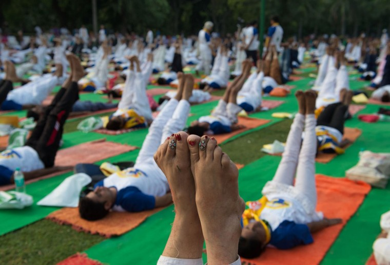 An Indian woman points her toes upwards in a morning yoga session held to mark International Yoga Day in Lodhi Gardens in New Delhi on June 21, 2016. / (AFP PHOTO / ROBERTO SCHMIDT)