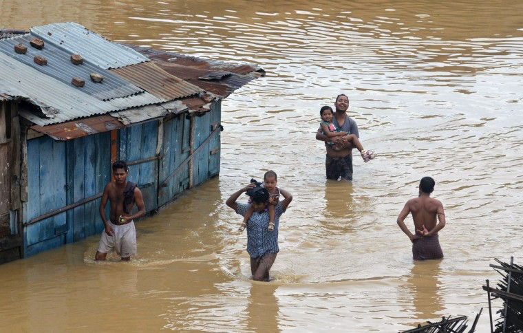 Residents wade through flood waters after heavy monsoon rain in Dimapur on June 28, 2016. Thousands of people were flooded out of their homes in India's northeastern state of Nagaland following heavy monsoon rains. (Caisii Mao/AFP/Getty Images)