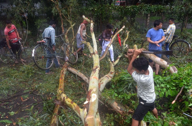 Indian pedestrians walk pass a fallen tree being chopped up on a road after heavy monsoon rains and high winds in Dimapur on June 28, 2016. Thousands of people were flooded out of their homes in India's northeastern state of Nagaland following heavy monsoon rains. (Caisii Mao/AFP/Getty Images)