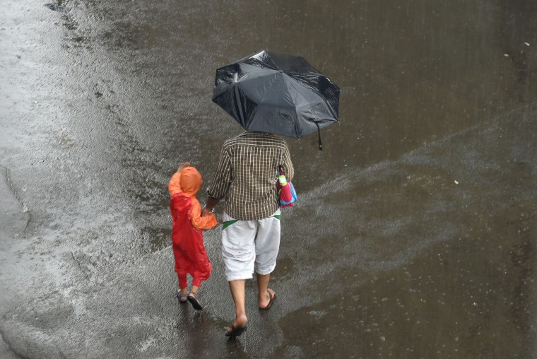 A man walks with a child protected by a raincoat during a downpour in Mumbai on June 20, 2016. Annual monsoon rains have progressed to parts of western and central India, easing fears of millions of desperate farmers after two straight years of drought, the weather department said. Farmers rely on the monsoon rains, which hit the Kerala coast every year and then sweep across the country, to water their crops and replenish dams and reservoirs. The arrival of the monsoon is always keenly watched in India, but even more so this year as much of the country reels from the drought. (Indranil Mukherjee/AFP/Getty Images)