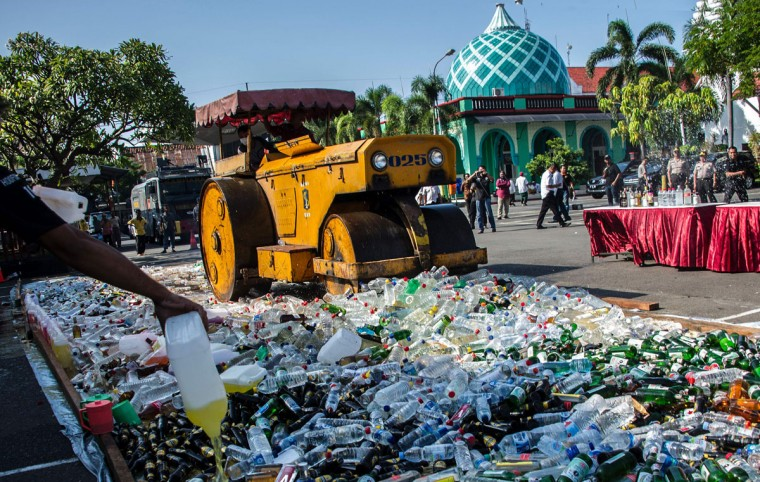 A steamroller runs over bottles of alcohol at a police station ahead of the holy Muslim month of Ramadan in Surabaya, East Java on June 2, 2016. Indonesia, the world's most populous Muslim-majority country, will begin Ramadan on June 6. / (AFP Photo/Juni Kriswanto)