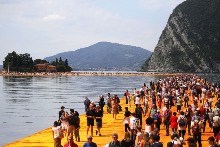People walk on the monumental installation entitled 'The Floating Piers' created by artist Christo Vladimirov Javacheff on Iseo Lake, in northern Italy, on June 18, 2016. (MARCO BERTORELLO/AFP/Getty Images)