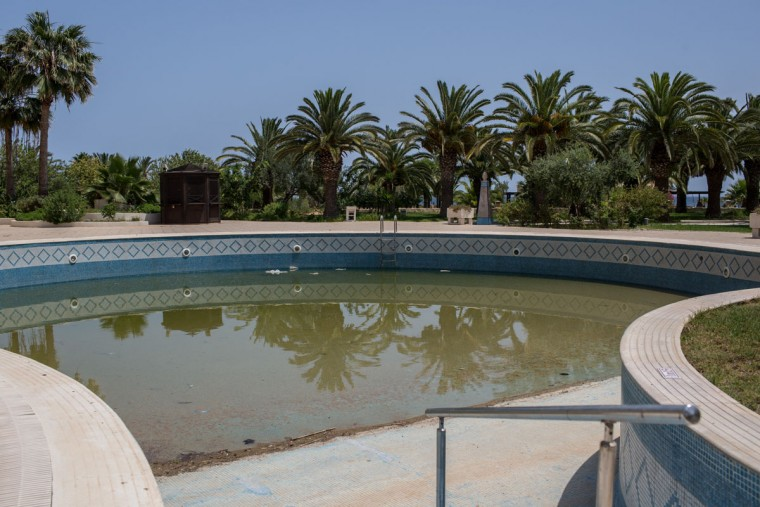The main swimming pool is seen at the closed Imperial Marhaba Hotel on June 24, 2016 in Sousse, Tunisia. The Imperial Marhaba hotel was the main target of the 2015 Sousse beach terrorist attack that killed 38 people including 30 Britons. The hotel attempted to stay open for three months after the attacks, however low occupancy forced the hotel to close. Since then it has operated with a skeleton staff, who work to maintain the rooms and grounds, other permanent hotel staff were able to be placed in temporary jobs at two other hotels owned by the same chain. The hotel hopes to open again by next spring or as soon as British travel advisories and restrictions are lifted for Tunisia. Before the 2011 revolution, tourism in Tunisia accounted for approximately 7% of the countries GDP. The two 2015 terrorist attacks at the Bardo Museum and Sousse Beach saw tourism numbers plummet even further forcing hotels to close and many tourism and hospitality workers to lose their jobs. The 26th of June 2016 marks the anniversary of the Sousse beach attacks. (Photo by Chris McGrath/Getty Images)