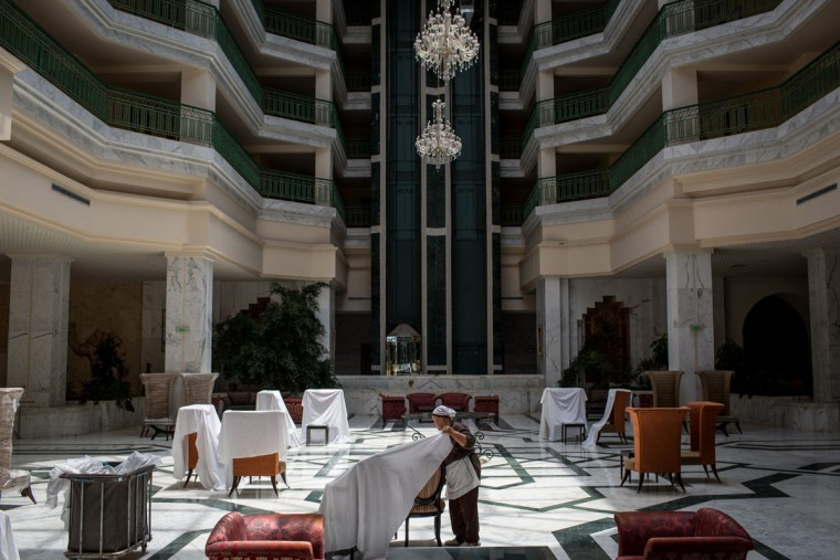 An employee throws sheets over lobby furniture at the closed Imperial Marhaba Hotel on June 24, 2016 in Sousse, Tunisia. The Imperial Marhaba hotel was the main target of the 2015 Sousse beach terrorist attack that killed 38 people including 30 Britons. The hotel attempted to stay open for three months after the attacks, however low occupancy forced the hotel to close. Since then it has operated with a skeleton staff, who work to maintain the rooms and grounds, other permanent hotel staff were able to be placed in temporary jobs at two other hotels owned by the same chain. The hotel hopes to open again by next spring or as soon as British travel advisories and restrictions are lifted for Tunisia. Before the 2011 revolution, tourism in Tunisia accounted for approximately 7% of the countries GDP. The two 2015 terrorist attacks at the Bardo Museum and Sousse Beach saw tourism numbers plummet even further forcing hotels to close and many tourism and hospitality workers to lose their jobs. The 26th of June 2016 marks the anniversary of the Sousse beach attacks. (Photo by Chris McGrath/Getty Images)