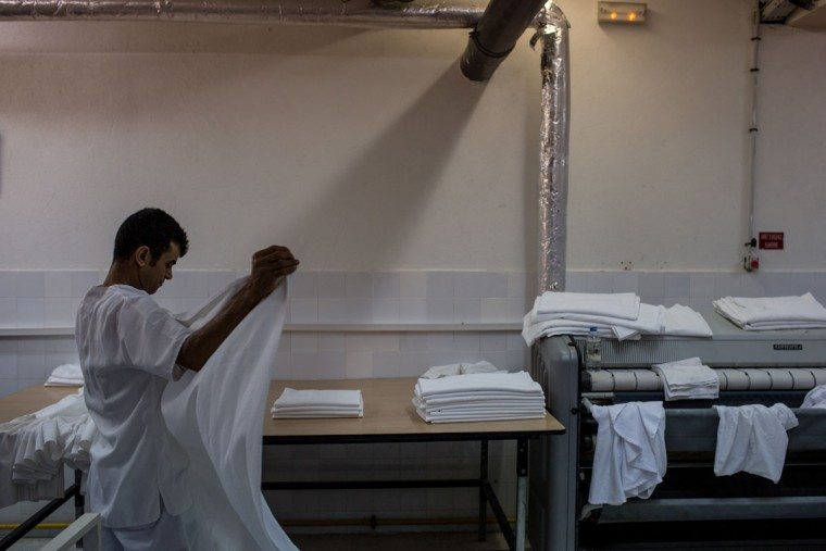 An employee folds sheets in the laundry of the closed Imperial Marhaba Hotel on June 24, 2016 in Sousse, Tunisia. The Imperial Marhaba hotel was the main target of the 2015 Sousse beach terrorist attack that killed 38 people including 30 Britons. The hotel attempted to stay open for three months after the attacks, however low occupancy forced the hotel to close. Since then it has operated with a skeleton staff, who work to maintain the rooms and grounds, other permanent hotel staff were able to be placed in temporary jobs at two other hotels owned by the same chain. The hotel hopes to open again by next spring or as soon as British travel advisories and restrictions are lifted for Tunisia. Before the 2011 revolution, tourism in Tunisia accounted for approximately 7% of the countries GDP. The two 2015 terrorist attacks at the Bardo Museum and Sousse Beach saw tourism numbers plummet even further forcing hotels to close and many tourism and hospitality workers to lose their jobs. The 26th of June 2016 marks the anniversary of the Sousse beach attacks. (Photo by Chris McGrath/Getty Images)
