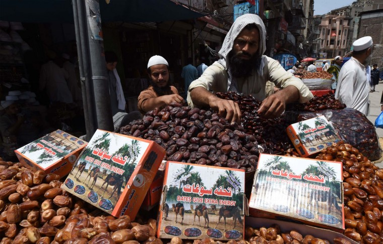 A Pakistani vendor arranges dates at a market ahead of the Islamic holy month of Ramadan in Peshawar on June 2, 2016. Muslims are preparing for Islam's holy month of Ramadan, which is calculated on the sighting of the new moon, and during which they fast from dawn until dusk. / (AFP Photo/A Majeed)