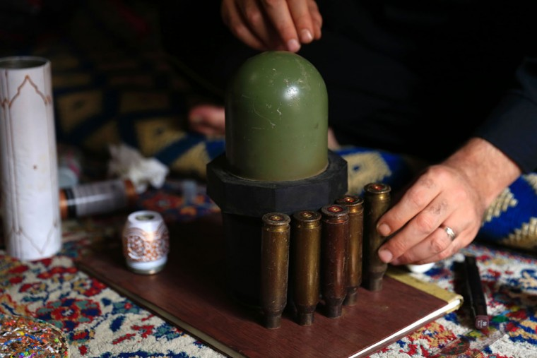 Syrian artist Akram Abu Elfoz works at his house on a model of the al-Rawdah mosque which he is building using bullet shells, cartridges and war leftovers, in the rebel-held town of Douma, east of the capital Damascus, on May 26, 2016. In his most recent project Akram, 37, creates downscaled models of important sites which have been destroyed by the ongoing conflict through using war leftovers, to creatively recreate and document places and buildings that have suffered severe damage. (AFP PHOTO / Sameer Al-Doumy)